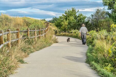 WINDSOR, CO, USA, SEPTEMBER 5, 2015: Morning walk with a dog on Poudre River Trail - paved bike trail extending more than 20 miles between Timnath and Greeley. Editorial