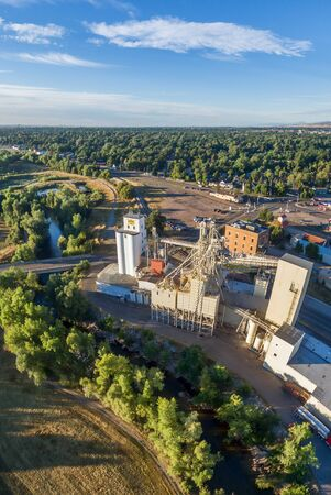 poudre river: FORT COLLINS, CO, USA - September 4,  2015: Aerial view of industrial landmarks on the shore of Poudre River - historic Harmony Mill built in 1886 and Ranch-Way Feeds grain elevators the oldest continuously running business in town.