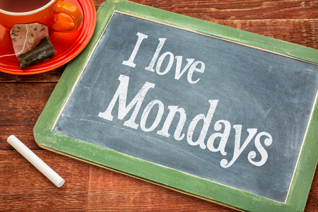 motivation: I love Mondays positive declaration - text on a slate blackboard with chalk and cup of tea Stock Photo