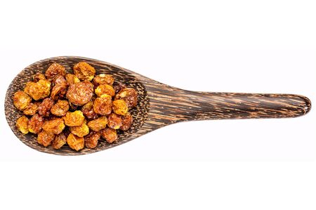 superfruit: dried goldenberries on a wooden spoon isolated on white - superfruit
