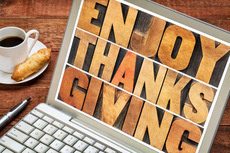 thanksgiving day: Enjoy  Thanksgiving  - word abstract in vintage letterpress wood type blocks on a laptop screen Stock Photo