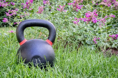 kettlebell: heavy iron competition kettlebell on green grass in a backyard - outdoor fitness concept