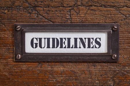 guideline: guidelines - file cabinet label, bronze holder against grunge and scratched wood Stock Photo