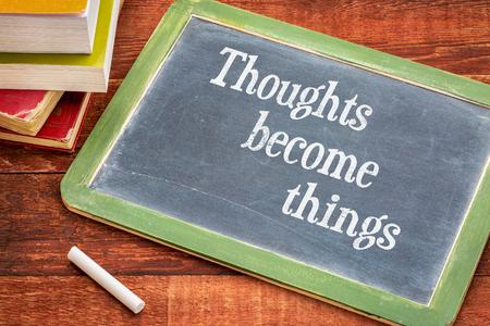 pensamientos se convierten en cosas - concepto de ley de la atracción - texto inspirado en una pizarra de la pizarra con una tiza blanca y una pila de libros sobre la mesa de madera rústica Foto de archivo