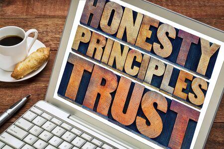 honestidad: honestidad, principios y la confianza concepto - palabras de tipograf�a vintage impresi�n de bloques tipo de madera manchados por tintas de color en una pantalla de ordenador port�til con una taza de caf�
