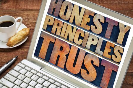 letterpress words: honesty, principles and trust concept - words in vintage letterpress wood type printing blocks stained by color inks on a laptop screen with a cup of coffee