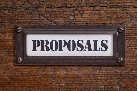 proposals: proposals  - file cabinet label, bronze holder against grunge and scratched wood Stock Photo