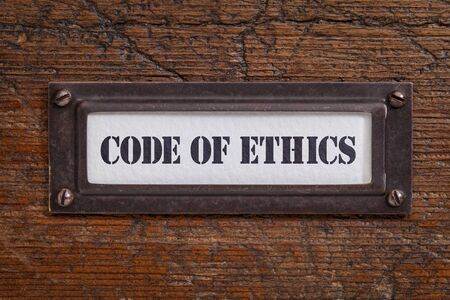 code of ethics  - file cabinet label, bronze holder against grunge and scratched wood