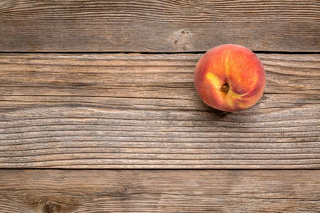 grained: single fresh peach fruit on weathered grained wood with a copy space Stock Photo