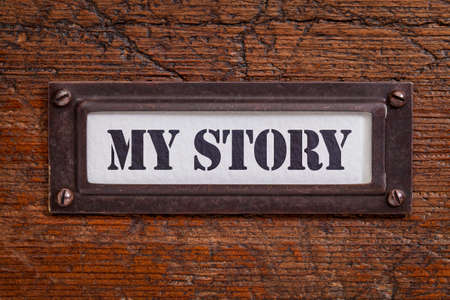 my story -  file cabinet label, bronze holder against grunge and scratched wood