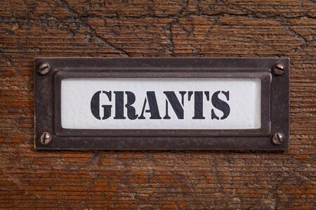 business funds: grants  - file cabinet label, bronze holder against grunge and scratched wood, financial concept
