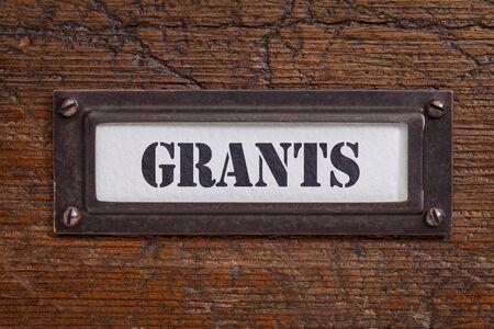 grants  - file cabinet label, bronze holder against grunge and scratched wood, financial concept Stock fotó - 45735944