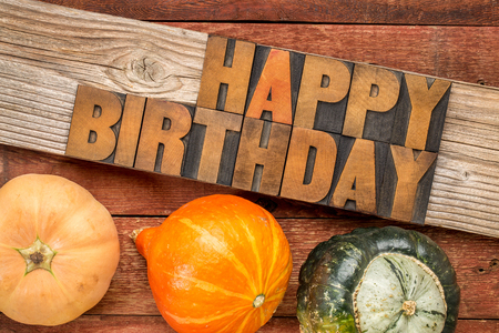 grained: Happy Birthday greeting card - text in letterpress wood type printing blocks over rustic grained barn wood with winter squash