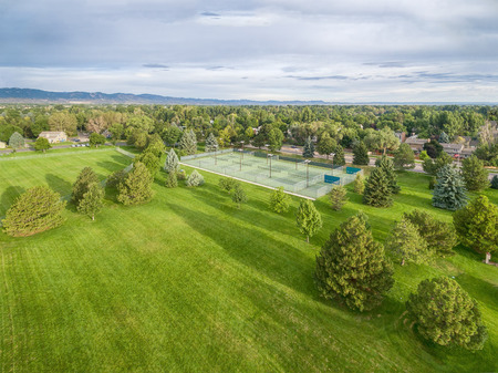 collins: aerial view of one of parks in Fort Collins, Colorado, with a large grass field and tennis courts, summer morning