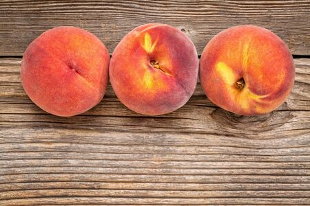 space wood: three fresh yellow  peach fruits on weathered grained wood with a copy space