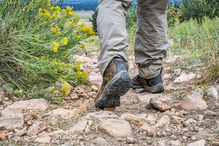 hiking boot: male feet in hiking leather boots on  a rocky mountain uphill trail