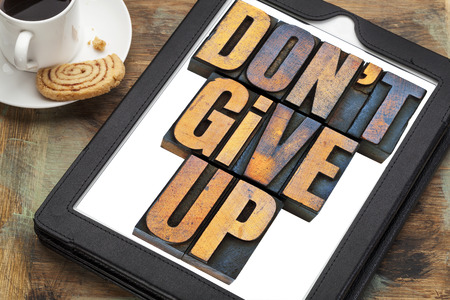 not give: do not give up - motivation concept - a phrase in vintage letterpress wood type printing blocks on a digital tablet with a cup of coffee Stock Photo
