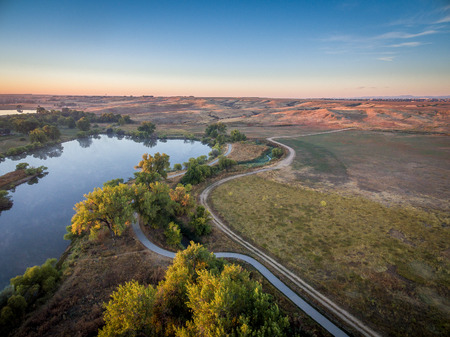 cache la poudre: aerial view of sunrise over Poudre River Trail with a bike path, ranch road and ponds
