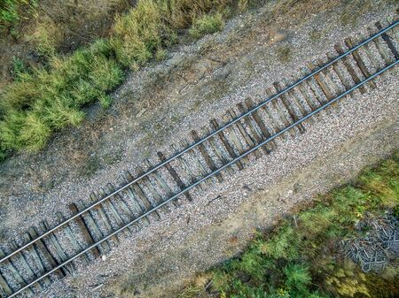 wood railroad: aerial view of single railroad tracks in back country with some weeds and trash Stock Photo
