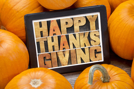 Happy Thanksgiving word abstract in letterpress wood type on a digital tablet surrounded by pumpkins Stock Photo