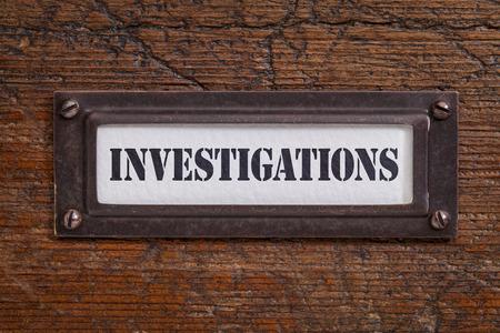 investigacion: investigaciones - etiqueta archivador, titular de bronce contra grunge y madera rayado
