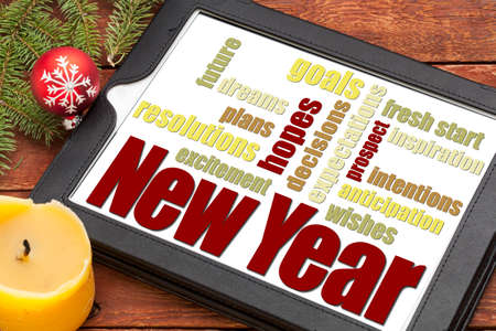 New Year goals. plans and expectations - a word cloud on a digital tablet with holiday decoration