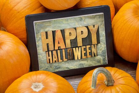 greeting cards: Happy Halloween - word abstract in letterpress wood type on a digital tablet surrounded by pumpkins