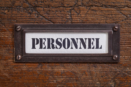 personnel  - file cabinet label, bronze holder against grunge and scratched wood Stock Photo