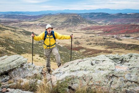 red mountain open space: senior male hiker reaching top of a rock cliff and gasping for air, REd MOuntain Open Space near Fort Collins, Colorado, early fall