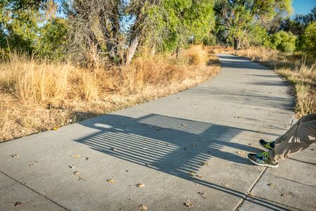 bike trail: bike trail with a shadow of man resting on a bench - Poudre River Corridor Trail in northern Colorado, late summer Stock Photo