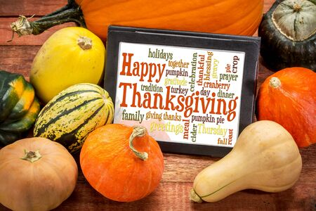 word cloud: Happy Thanksgiving word cloud on a digital tablet surrounded by pumpkin and winter squash Stock Photo