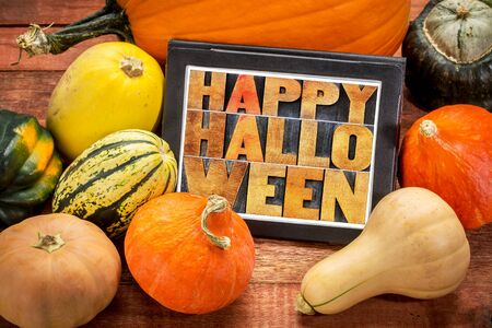 Happy Halloween - abstract text in letterpress wood type on a digital tablet surrounded by pumpkin and winter squash