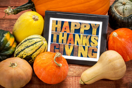 happy thanksgiving: Happy Thanksgiving word abstract in letterpress wood type on a digital tablet surrounded by pumpkin and winter squash Stock Photo