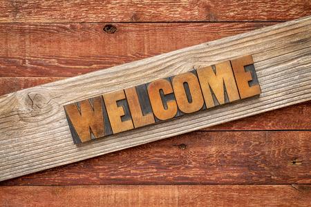 the welcome: r�stico cartel de bienvenida - letterpress tipo de madera sobre tabla de cedro de grano contra la madera del granero rojo
