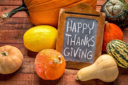 Happy Thanksgiving - wit krijt handschrift op een klein bord, omringd door pompoen en winter squash