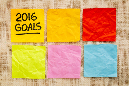 new year: 2016 New Year goals - handwriting on a sticky note against grained wood with blank notes
