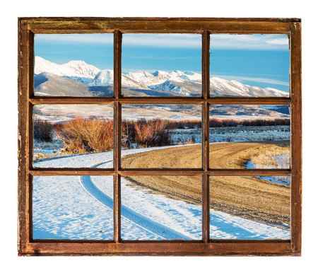 bow window: travel concept - a view of windy  road and snowy mountains  through vintage, grunge, sash window with dirty glass  - Medicine Bow Mountains, Colorado