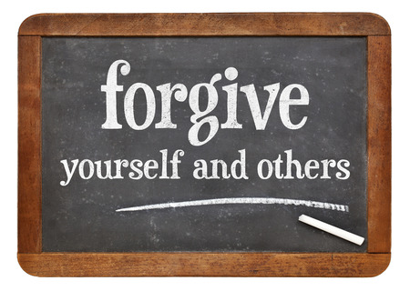 Forgive yourself and others advice - white chalk text n on a vintage slate blackboard