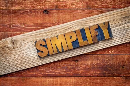 simplify: simplify word rustic sign - letterpress wood type over grained cedar plank against red barn wood