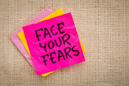 self development: Face your fears advice or reminder on a sticky note against canvas