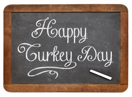 Happy Turkey Day - white chalk handwriting on a vintage slate blackboard isolated on white, Thanksgivieng greetings