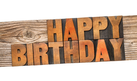 wood type: Happy Birthday greeting card - text in letterpress wood type printing blocks on a grained cedar plank  isolated on white Stock Photo