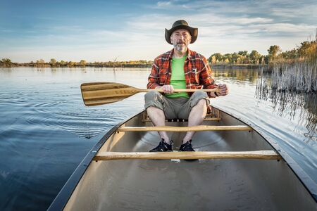collins: senior paddler enjoying paddling a canoe on a calm lake, Riverbend Ponds Natural Area, Fort Collins, Colorado Stock Photo