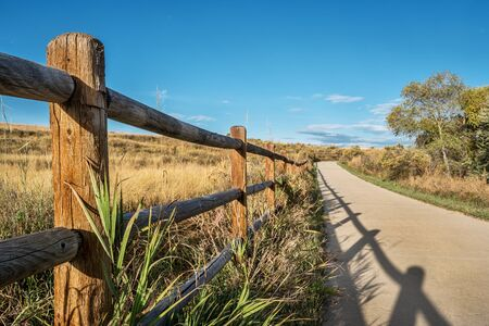 poudre river: wooden fence with a shadow and a  bike trail  - Poudre River Trail in northern Colorado near Windsor. It is a  paved path  extending more than 20 miles between Timnath and Greeley. Stock Photo