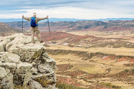 red mountain open space: male hiker reaching top of a rock cliff and looking at scenery of Red Mountain Open Space near Fort Collins, Colorado, early fall