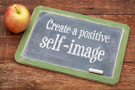 self image: Create positive self image - inspirational words on a slate blackboard against red barn wood Stock Photo