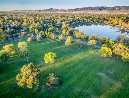 fort collins: aerial view of a lake and park in fall colors under morning light with deep long shadows, Fort Collins, Colorado,