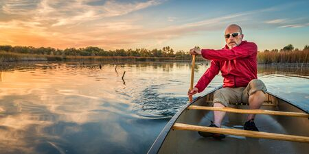 paddling: senior paddler enjoying paddling a canoe on a calm lake at sunset, Riverbend Ponds Natural Area, Fort Collins, Colorado