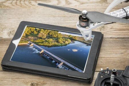drone aerial photography concept - reviewing aerial picture of a river diversion dam on a digital tablet with a drone rotor and radio control transmitter,