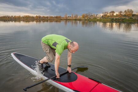 paddleboard: senior male is starting  paddling workout on his stand up paddleboard on a lake in Colorado